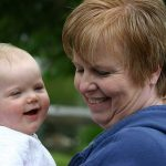 Redheaded grandmother holding happy baby girl