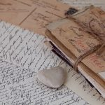 vintage style still life with bundle of old handwritten letters and a stone heart