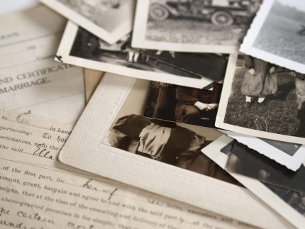 Pile of black and white photos and documents for a biography or autobiography