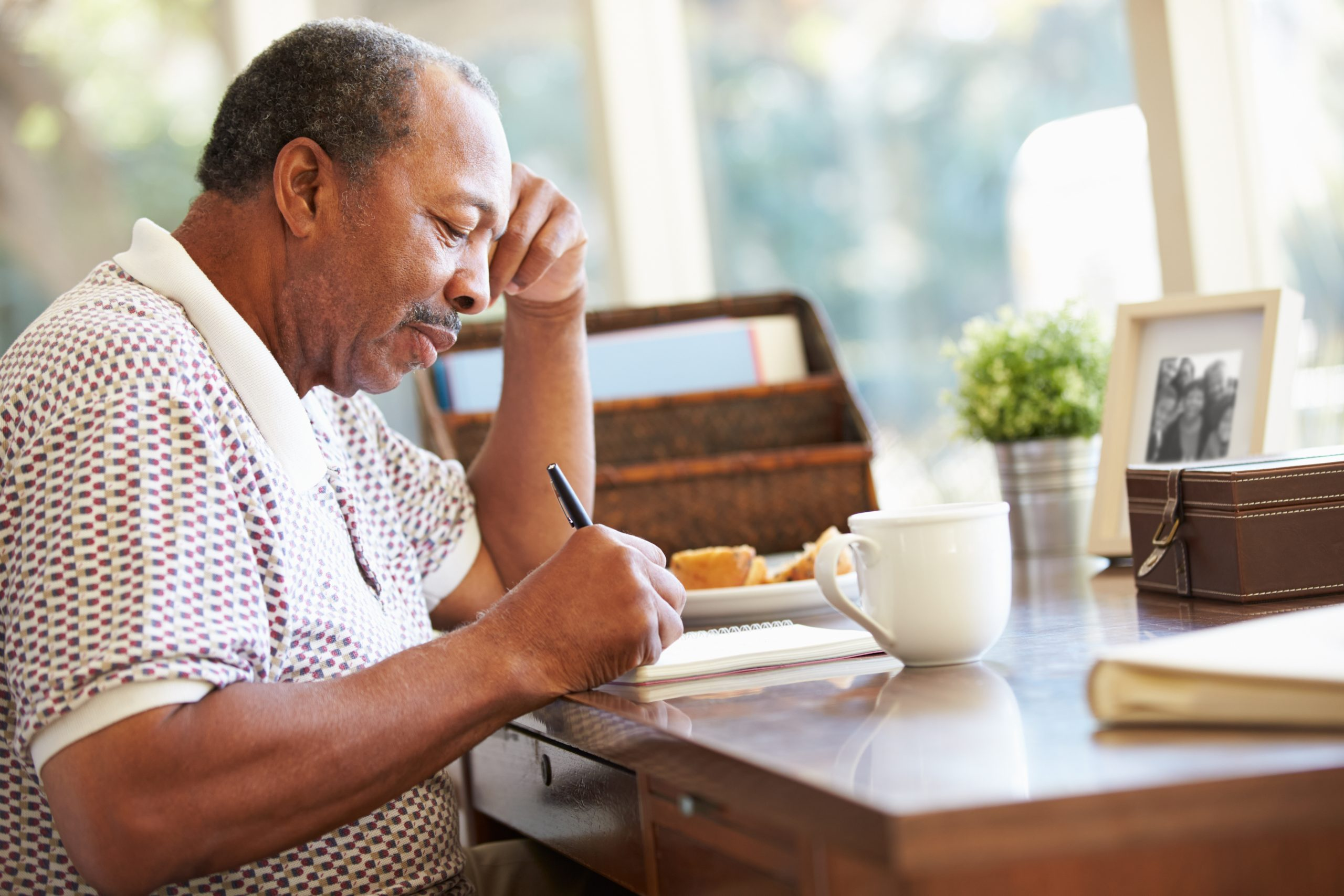 Senior man sitting at table writing his autobiography