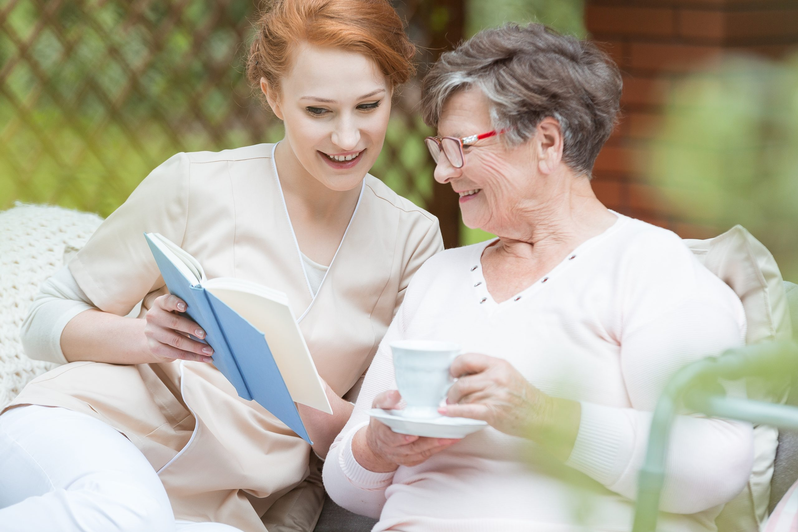Younger woman sitting next to senior woman looking at her autobiography