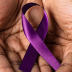 Two hands hold a purple ribbon for Alzheimers awareness