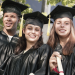 Four high school seniors celebrate graduation day in their gowns and caps